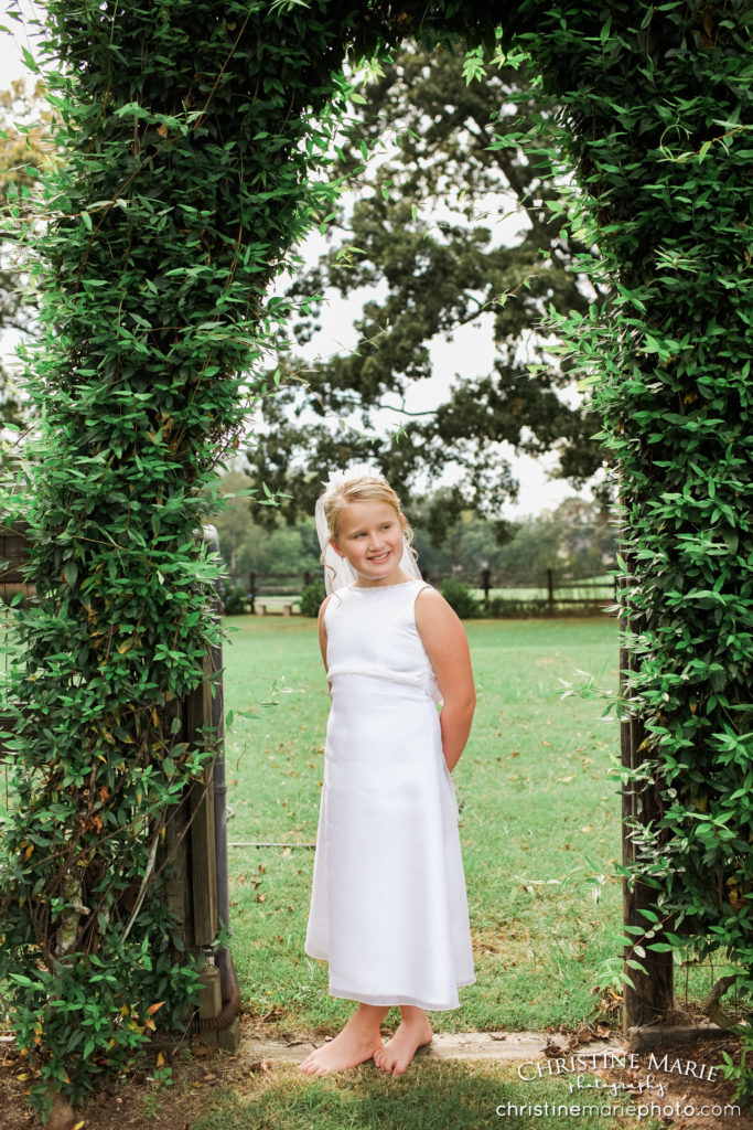 little girl in first holy communion dress under ivy arch