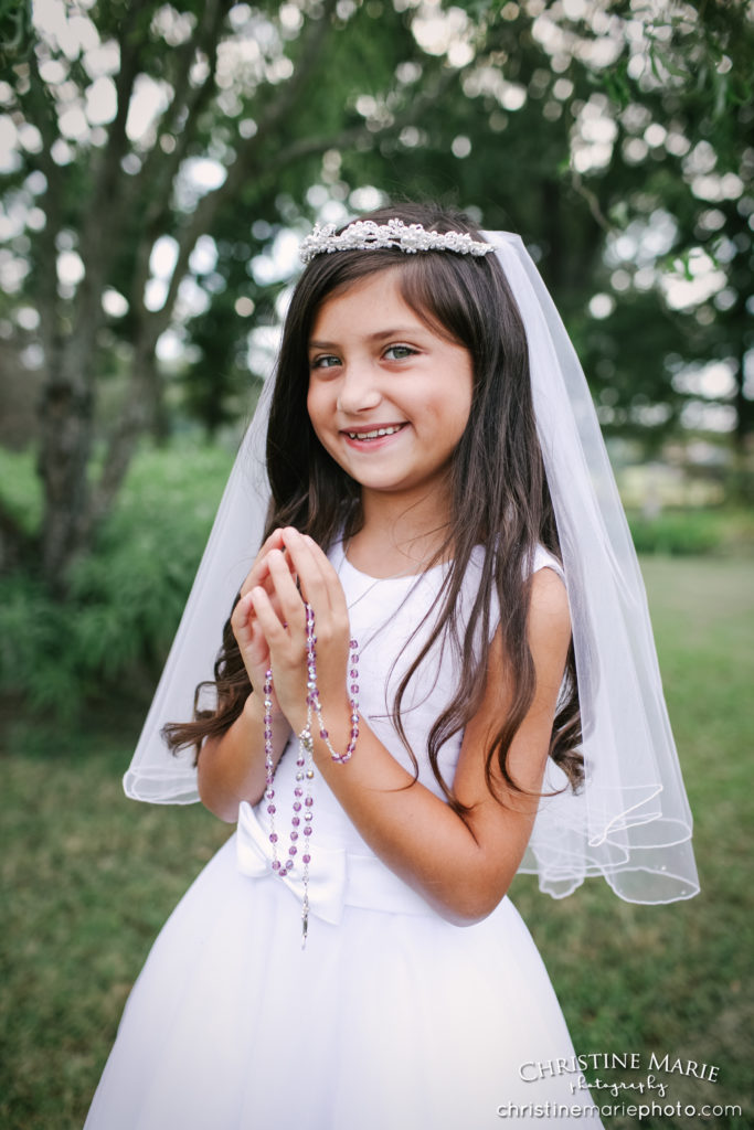 little girl holding rosary for first holy communion