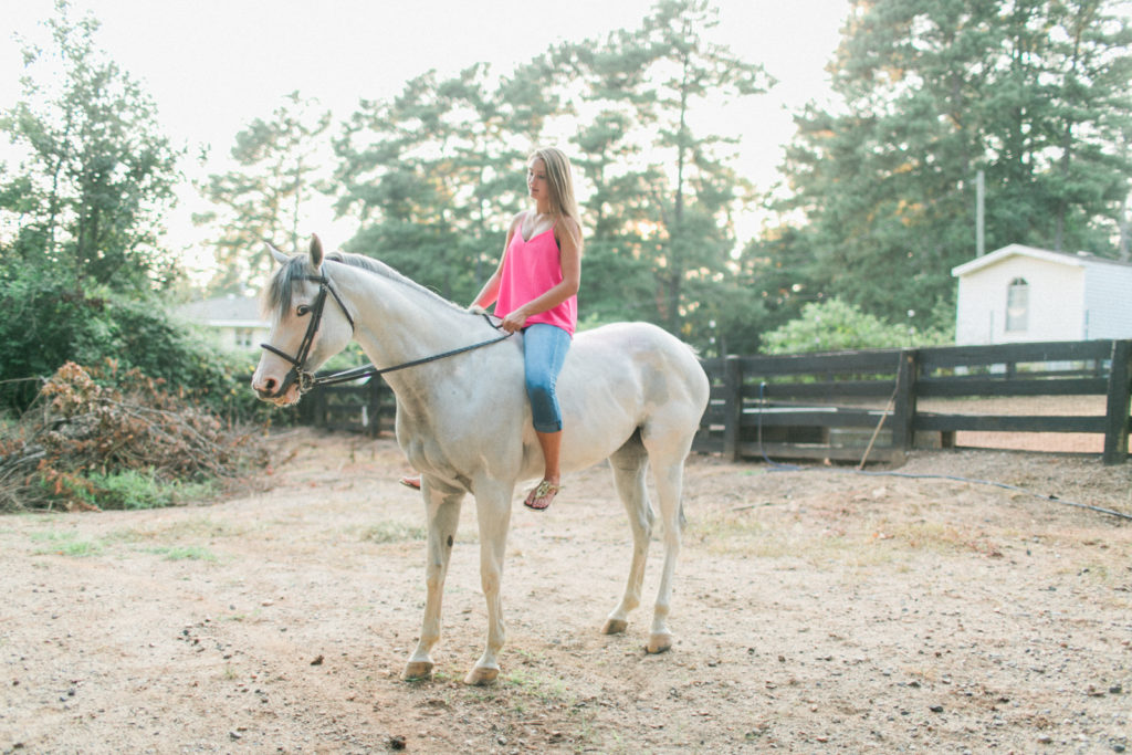 teenage girl riding white horse