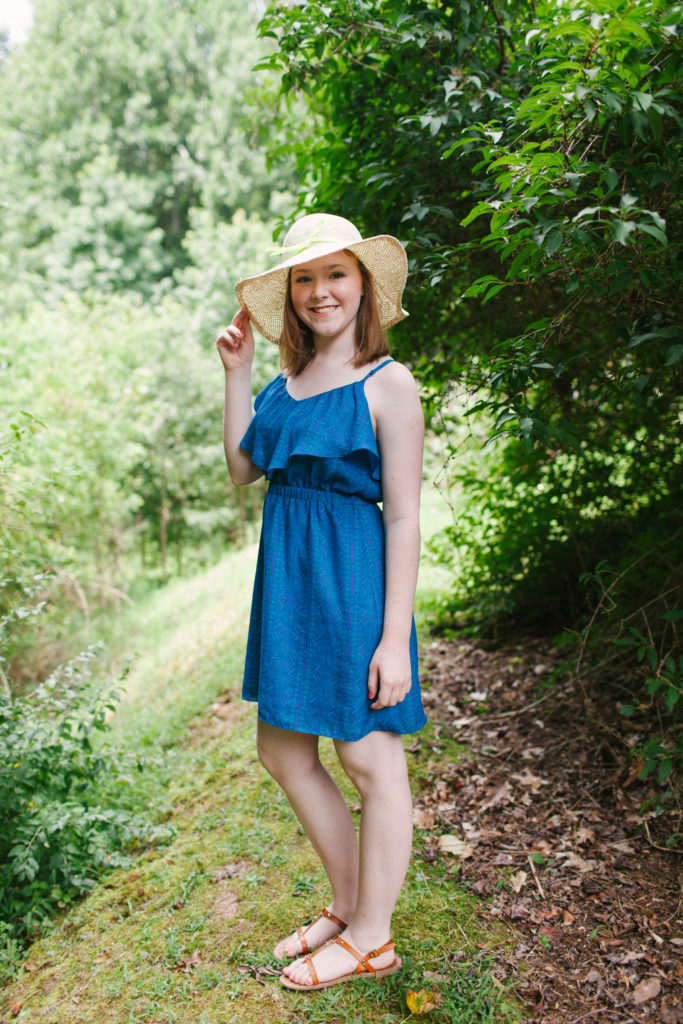 teenage girl in blue dress and floppy hat