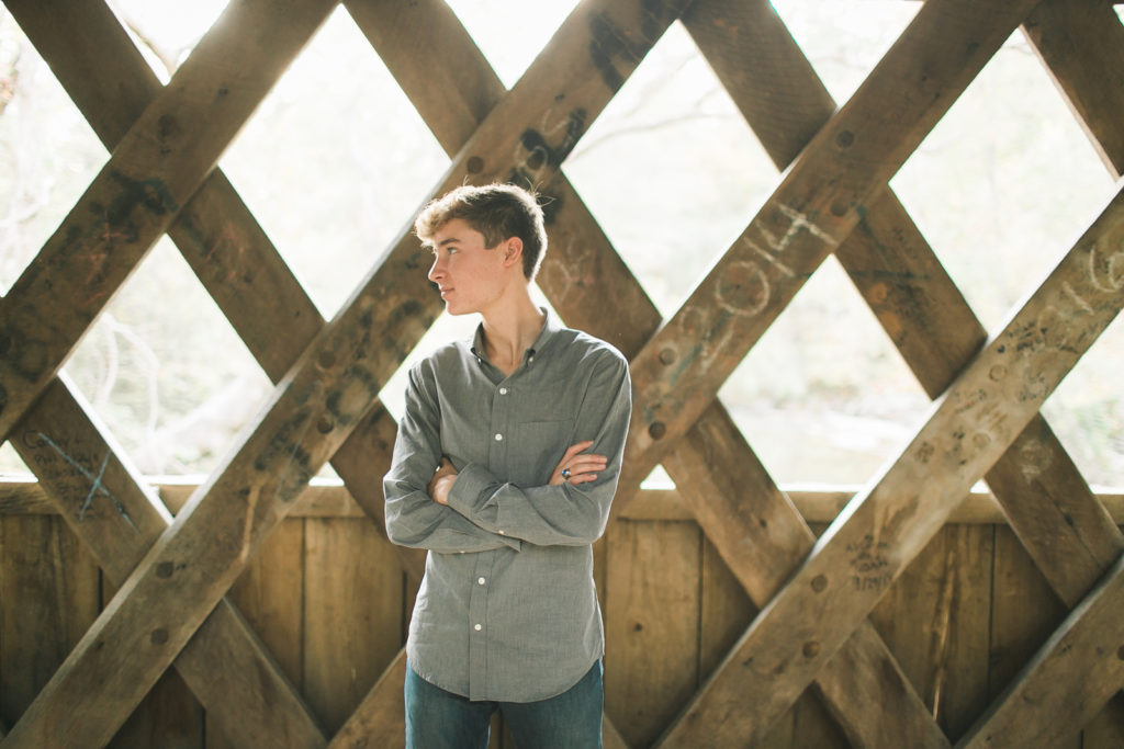 teenage boy senior photos in a bridge