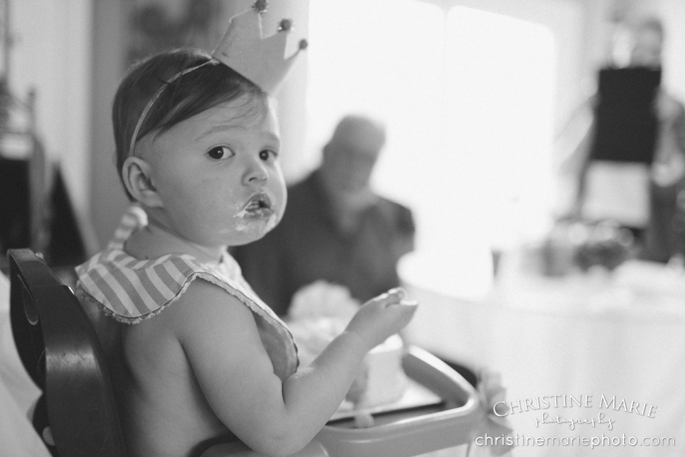 one year old girl stuffing her face with cake