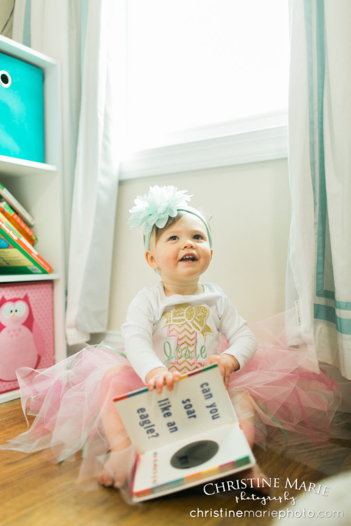 happy baby girl with her flower headband and books