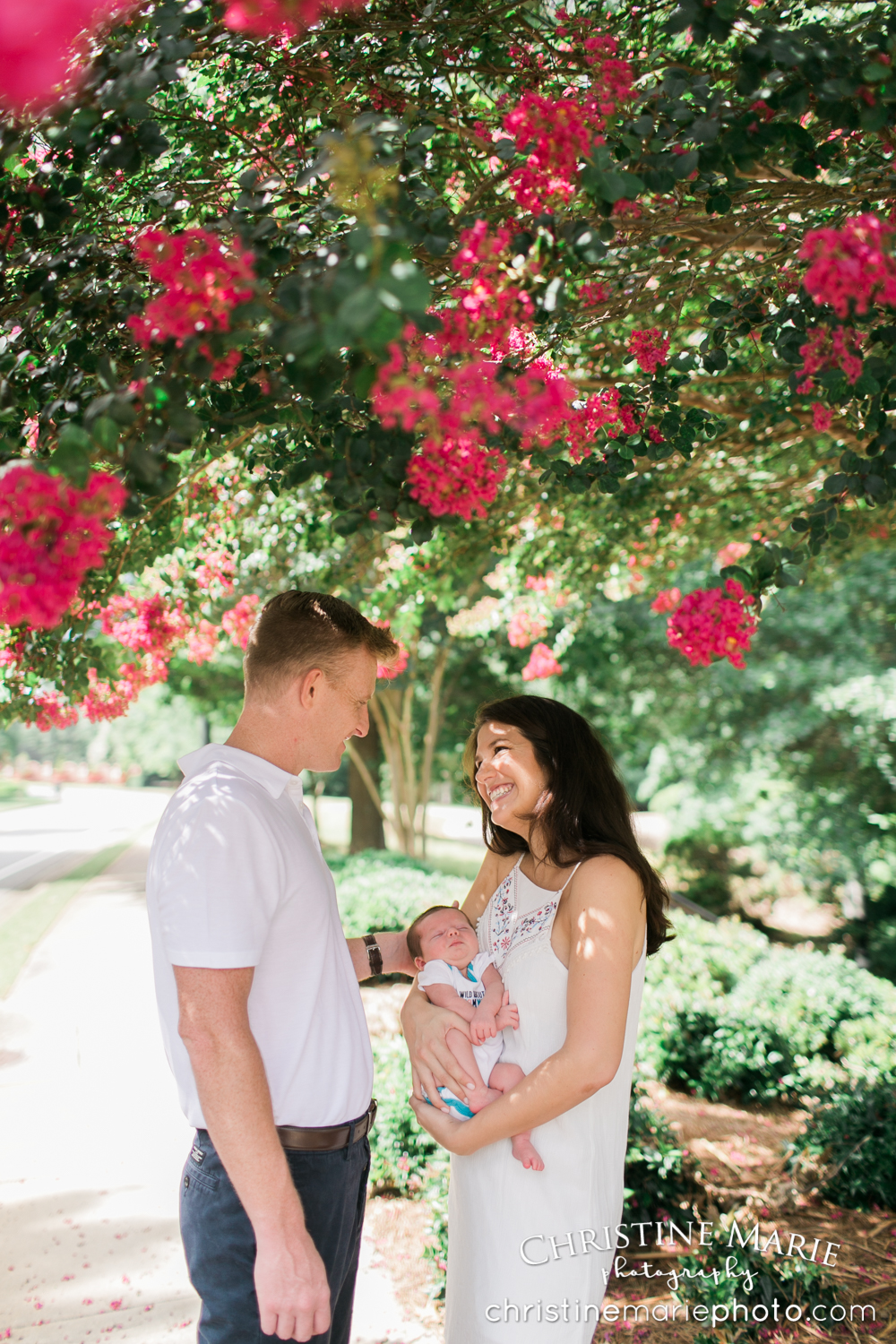 happy couple with their new baby under flowering pink tree