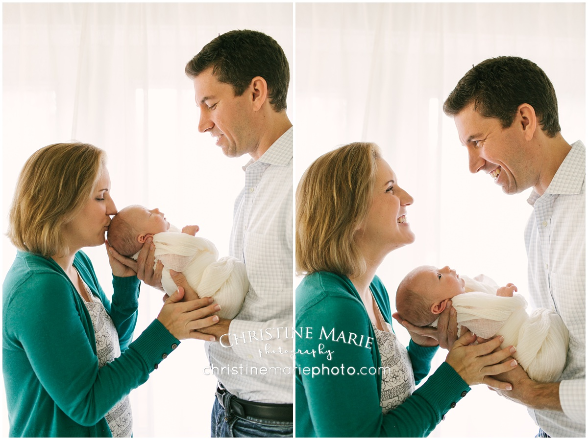 backlit happy mom and dad with newborn